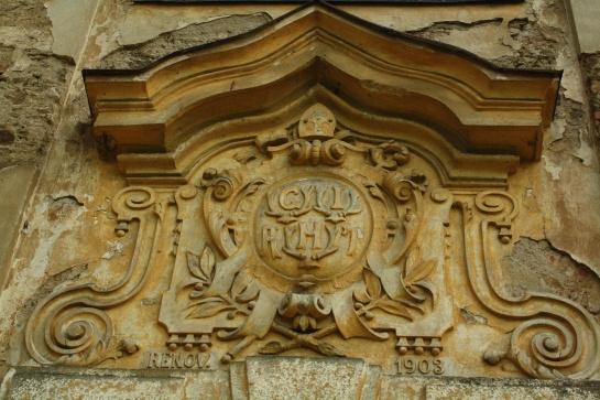 Erb nad vchodem do kostela ve Skocích